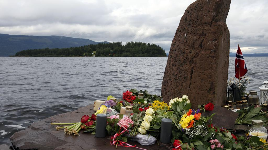 Breiviksagen fredag Flowers and candles are seen on the shore in front of Utoeya island northwest of Oslo