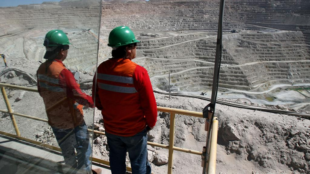 FILE PHOTO: Workers at BHP Billiton''s Escondida, the world''s biggest copper mine, are seen in front of the open pit, in Antofagasta,