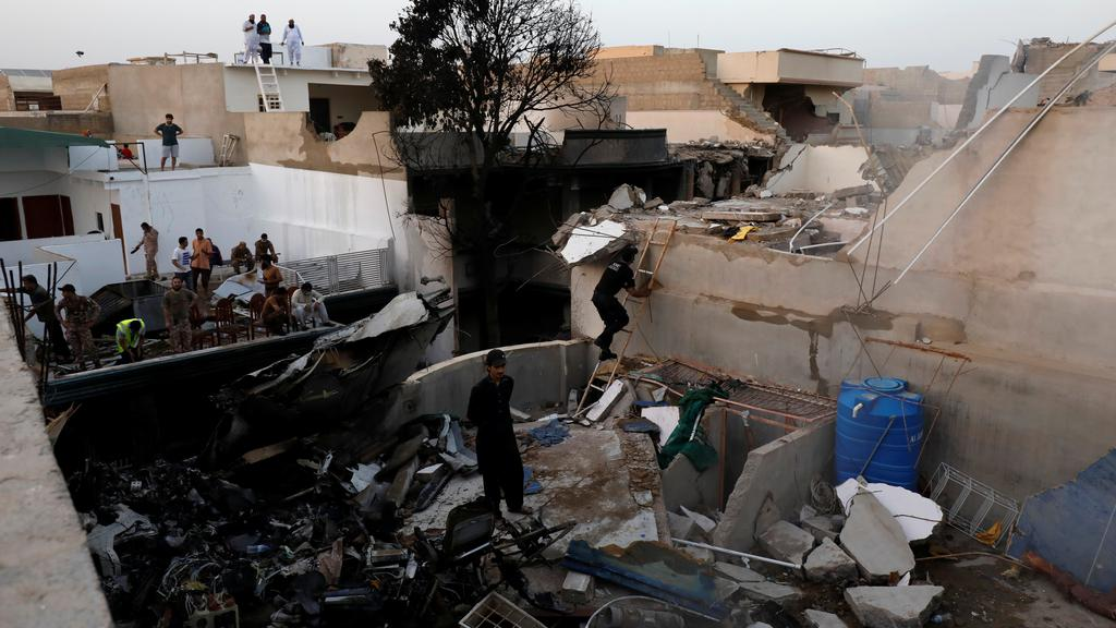 People stand on a roof of a house amidst debris of a passenger plane, crashed in a residential area near an airport in Karachi
