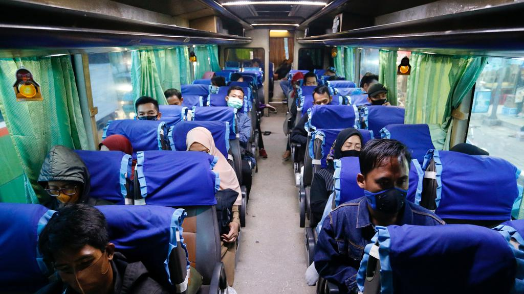 Passengers wearing protective face mask sit in a bus at a main bus station amid the outbreak of the coronavirus disease (COVID-19) in Jakarta
