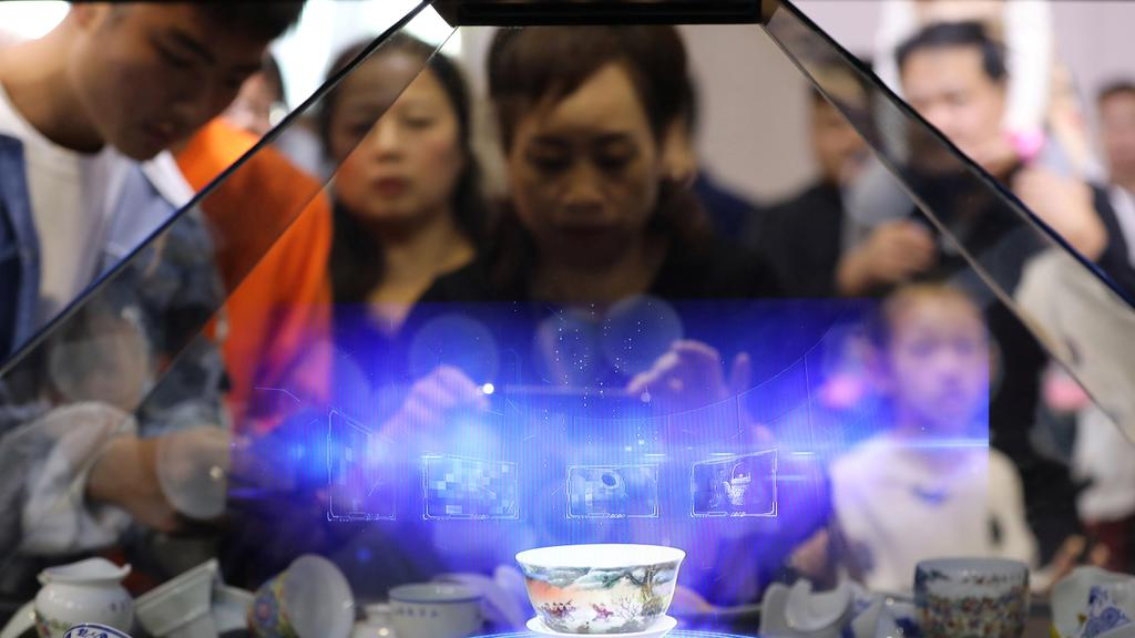 Visitors hold their phoners in front of a hologram showing a porcelain teacup that is projected inside a glass cabinet during the World Conference om VR Industry in Nanchang