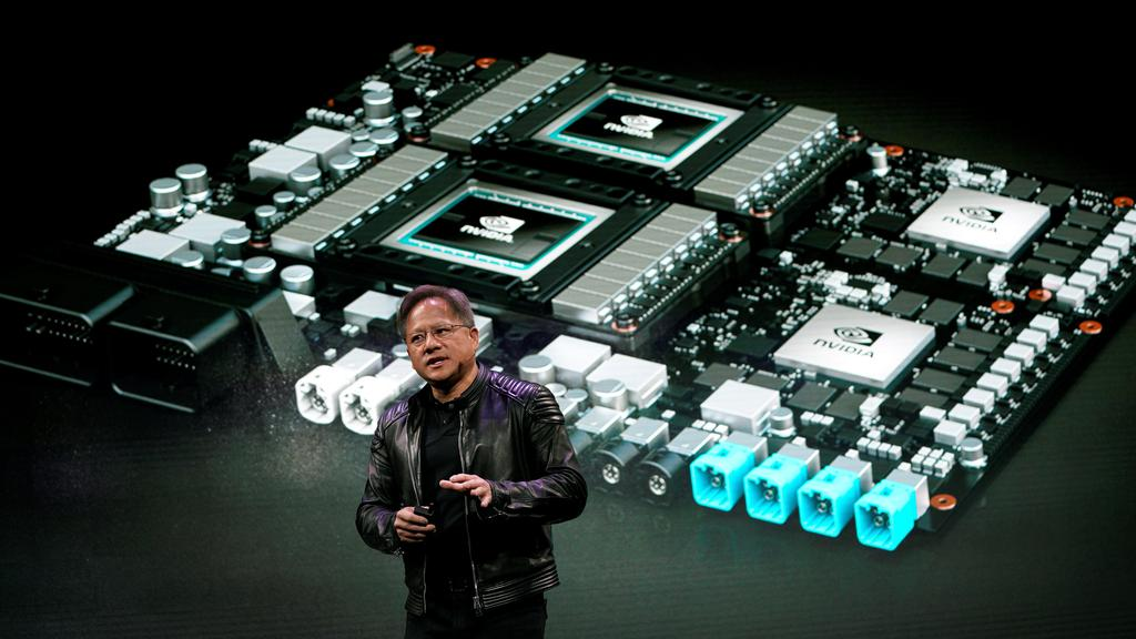 Jensen Huang, CEO of Nvidia, shows the Drive Pegasus robotaxi AI computer at his keynote address at CES in Las Vegas