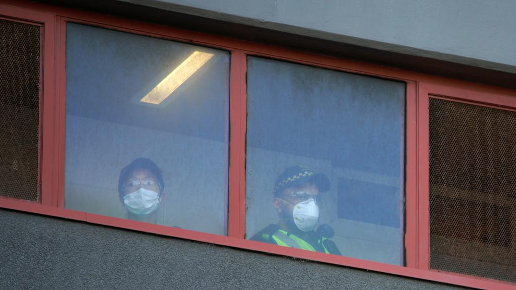 Police officers look out the windows of a public housing tower locked down in response to an outbreak of COVID-19 in Melbourne