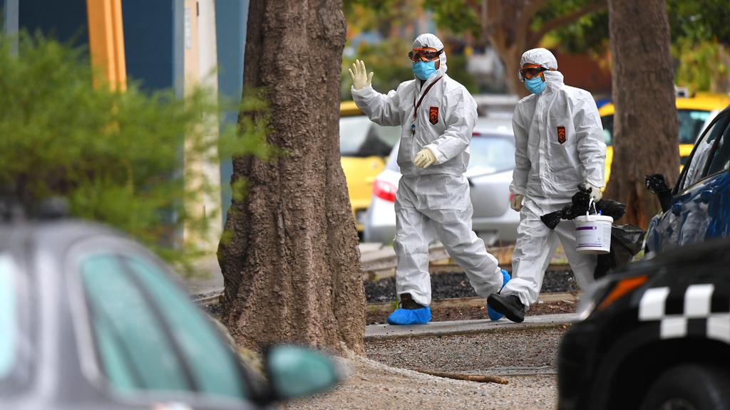 People in hazardous material overalls are seen outside of a public housing tower along Racecourse Road that was placed under lockdown due to the coronavirus disease (COVID-19) outbreak in Melbourne