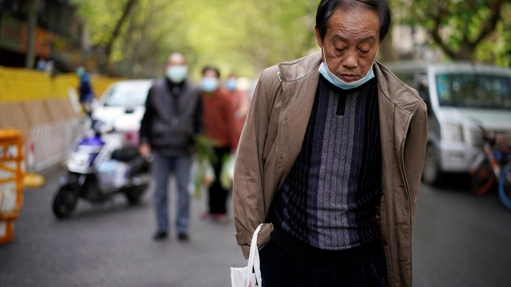 Man with a face mask observes a moment of silence on a street in Wuhan