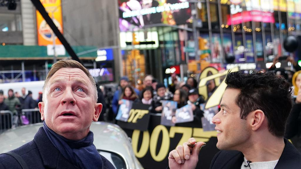 Actors Daniel Craig and Rami Malek talk as they look up at the lights during a promotional appearance on TV in Times Square for the new James Bond movie