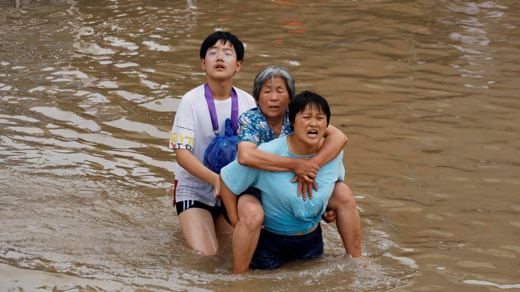 People make their way through floodwaters following heavy rainfall in Zhengzhou