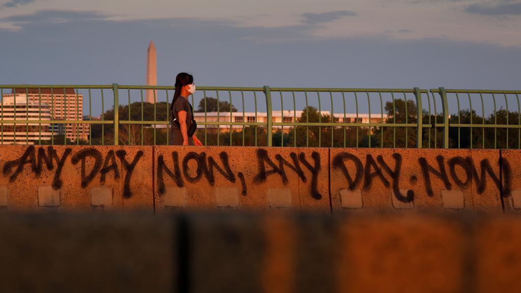 A masked pedestrian walks across the Key Bridge at sunset, amid the coronavirus disease (COVID-19) outbreak in Washington