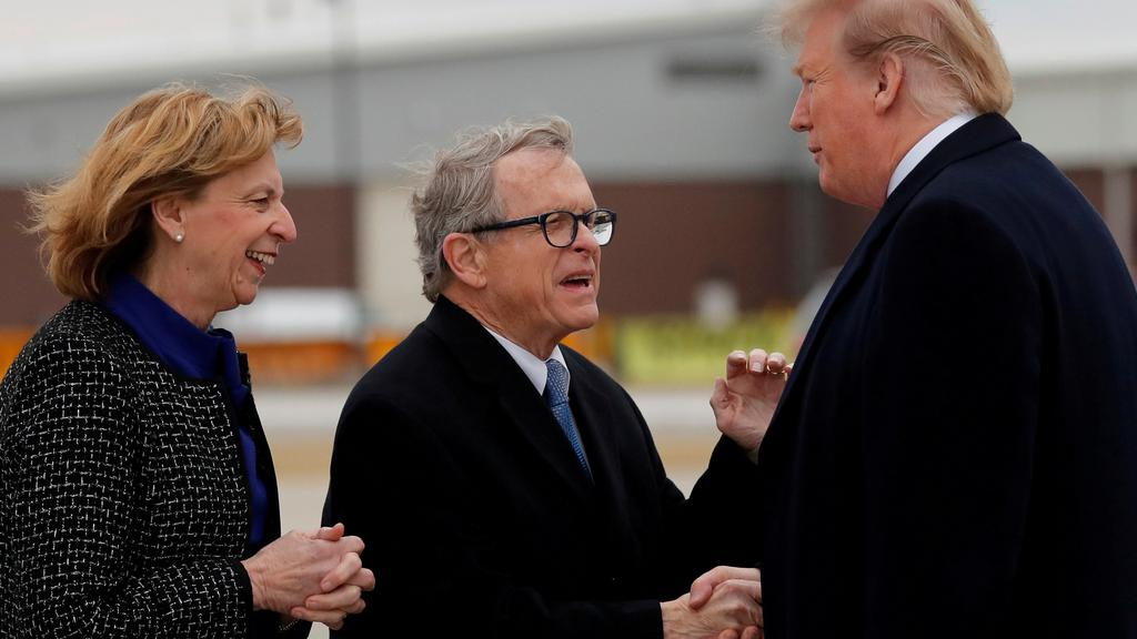 FILE PHOTO: U.S. President Donald Trump shakes hands with Governor of Ohio Mike DeWine as he arrives at Akron-Canton airport in Canton, Ohio, U.S.